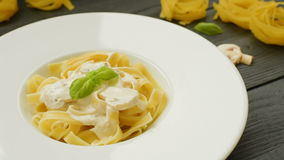 Pasta with mushrooms, basil and cream sauce stock video footage