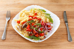 Pasta with mushrooms, cherry tomatoes and tomato sauce, italian food. Closeup Stock Photography