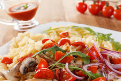 Pasta with mushrooms, cherry tomatoes and tomato sauce, italian food. Closeup Royalty Free Stock Photography