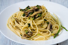 Pasta with mushrooms and green onions on a white plate on a wood Stock Photos