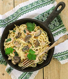 Pasta with mushrooms and meat in a creamy sauce. Spaghetti, oyster mushrooms, chicken and parsley Stock Image