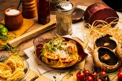Pasta, mushrooms and parma. A delicious pasta on a wooden table served on a plate. Olive oil, salt, spices and vinegar in background royalty free stock photos