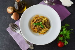 Pasta with mushrooms and pesto sauce in a white plate on abstract bckground. Italian lifestyle. Healthy eating concept. Stock Photography
