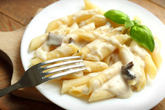 Pasta with mushrooms. Pasta with white mushroom sauce in a plate placed on the table Stock Photo
