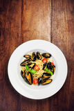 Pasta with mussels, cherry tomato  and basil in white plate on w Royalty Free Stock Photos