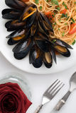 Pasta with mussels and cherry tomatoes on white background Royalty Free Stock Photos