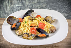 Pasta with mussels, clams and cherry tomatoes on wooden table Stock Images