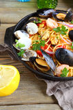 Pasta with mussels, squid and parsley in a frying pan Stock Photo