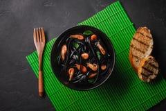 Pasta nera del Fettuccine dell'inchiostro del calamaro con i gamberetti o gamberetti, prezzemolo, peperoncino rosso in vino e sal fotografia stock libera da diritti