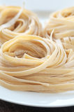 Pasta Nests. Homemade fettuccini noodles rolled into nests on white plate stock photography