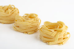 Pasta nests. Pasta Fettuccine close up isolated Royalty Free Stock Photos