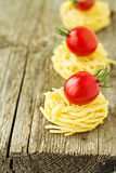 Pasta nests with cherry tomatoes Stock Images