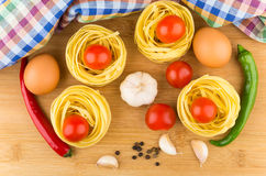 Pasta nests, eggs, tomatoes, garlic and chili peppers Stock Photo