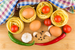 Pasta nests, eggs, tomatoes, garlic and chili peppers Royalty Free Stock Images