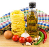 Pasta nests, eggs, tomatoes, garlic and oil bottle on board Stock Photos