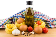 Pasta nests, eggs, tomatoes, garlic and oil bottle on board Stock Photo