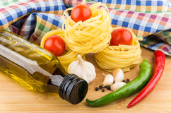 Pasta nests, eggs, tomatoes, garlic and oil bottle on board Royalty Free Stock Images
