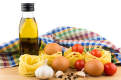 Pasta nests, eggs, tomatoes, garlic and oil bottle Royalty Free Stock Photography