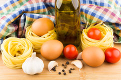 Pasta nests, eggs, tomatoes and oil on background of towels Royalty Free Stock Photo