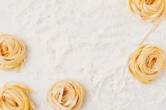 Pasta nests frame. Top view of pasta nests frame on table spilled in flour Royalty Free Stock Image