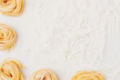 Pasta nests frame. Top view of pasta nests frame on table sprinkled in flour Stock Image