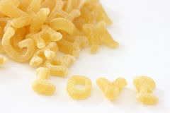 Pasta noodles in alphabet shapes forming word love Stock Photos