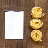 Pasta and notebook on old wooden table Royalty Free Stock Image