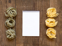 Pasta and notebook on old wooden table Royalty Free Stock Images