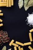Pasta och kryddor på en svart bakgrund arkivbild