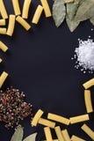 Pasta och kryddor på en svart bakgrund royaltyfri fotografi