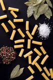 Pasta och kryddor på en svart bakgrund Royaltyfri Bild