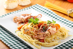 Pasta with octopus, tomatoes and carrots Royalty Free Stock Image