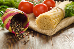 Pasta with oil, tomatoes, greens and papper on the wood. Pasta with olive oil, tomatoes, greens and papper on the wood Stock Photos