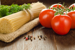 Pasta with oil, tomatoes, greens and papper on the wood. Pasta with olive oil, tomatoes, greens and papper on the wooden table Royalty Free Stock Photo