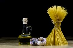 Pasta and olive oil on an old kitchen table. Recipes in old books in the kitchen on a wooden table. stock photography