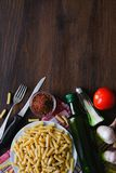 Pasta, olive oil, spices, tomatoes, salt, garlic, knife and fork lie on a dark wooden table. Top view with copy space. The concept stock photo