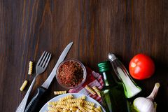 Pasta, olive oil, spices, tomatoes, salt, garlic, knife and fork lie on a dark wooden table. Top view with copy space. The concept stock images