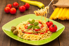 Pasta with olives. Fork with spaghetti with tomato sauce above plate Stock Photography