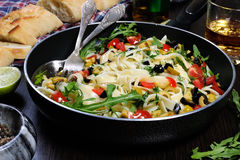 Pasta with olives and tomatoes. Pasta with crushed olives and cherry tomatoes, arugula. Horizontal shot Stock Photos
