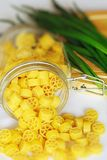 Pasta and onions. An image of bright yellow pasta in a jar and onions Royalty Free Stock Photo