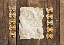 Pasta and paper on old wooden table Stock Photos
