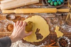 Pasta para cocer las galletas rizadas y la mano que sostienen un molde Aún-vida en un fondo de madera Imágenes de archivo libres de regalías