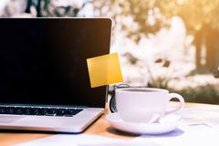 Pasta pegajosa da almofada de nota no portátil com o copo de café na mesa de madeira Foto de Stock