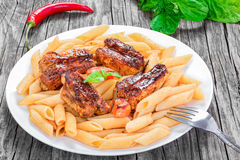 Pasta penne with appetizing grilled ribs Stock Photos