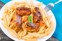 Pasta penne with appetizing grilled ribs with carrots and basil on an white dish on old wooden table, close-up Stock Images