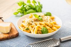 Pasta penne with chicken pieces mushrooms basil parmesan cheese and white wine. Italian food in white plate on kitchen. Pasta penne with chicken pieces mushrooms stock photography