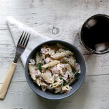 Pasta. Penne is cooked al dente, then mixed with sliced ham, feta cheese and basil. Dressing is made with olive oil, bit of vinegar, salt and pepper. Served stock photo