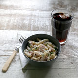 Pasta. Penne is cooked al dente, then mixed with sliced ham, feta cheese and basil. Dressing is made with olive oil, bit of vinegar, salt and pepper. Served royalty free stock photos