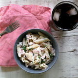 Pasta. Penne is cooked al dente, then mixed with sliced ham, feta cheese and basil. Dressing is made with olive oil, bit of vinegar, salt and pepper. Served royalty free stock photo
