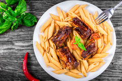 Pasta penne with grilled ribs, view from above Royalty Free Stock Images